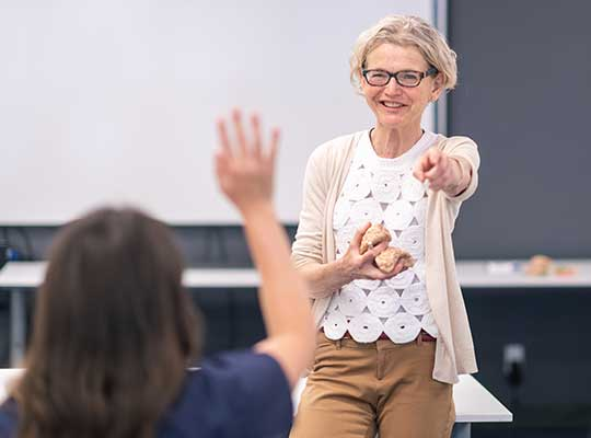 Master's in Education professor calls on a student raising their hand.